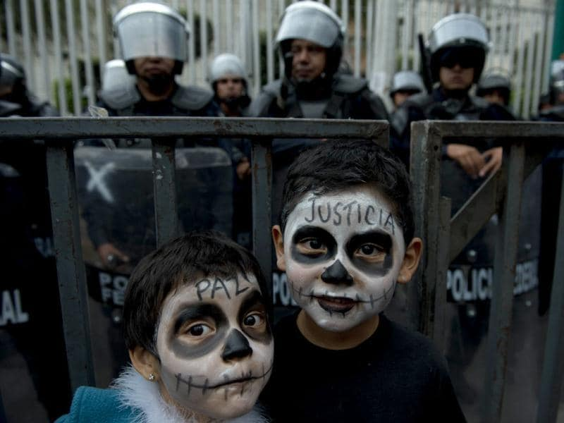 Children with their faces painted, accompany their mother in a demonstration in front of the Mexican Electoral Tribunal building. Enrique Pena Nieto was declared Mexico's president-elect after a two-month legal fight, but his leftist rival refused to accept the result and called for a rally. AFP/Yuri Cortez