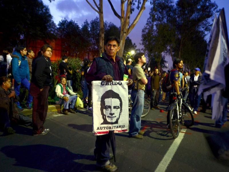 A man holds a placard with the face of Mexican President-elect Enrique Pena Nieto reading