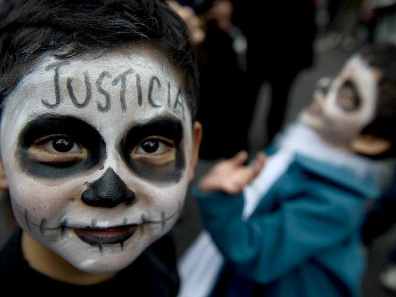 A boy with his face painted, accompanies his mother in a demonstration in front of the Mexican Electoral Tribunal building. Enrique Pena Nieto was declared Mexico's president-elect after a two-month legal fight, but his leftist rival refused to accept the result and called for a rally. AFP/Yuri Cortez