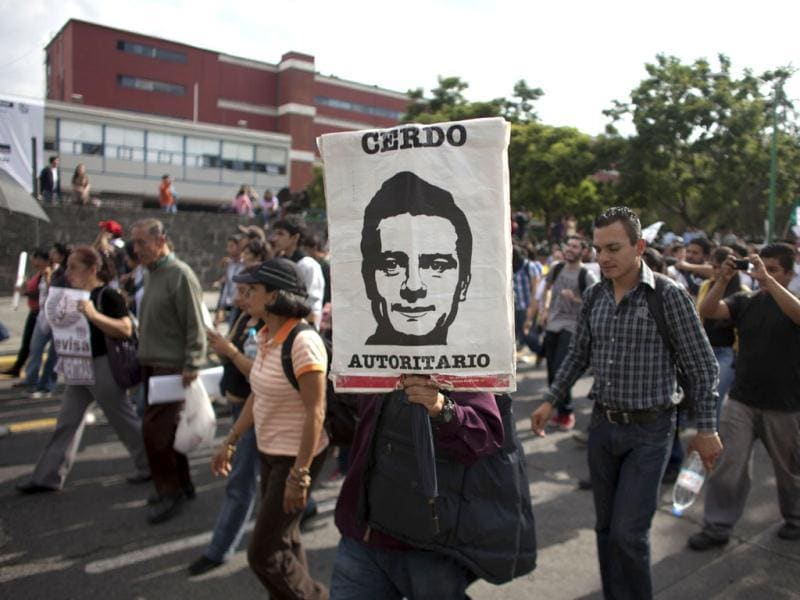 A demonstrator holds an image depicting Mexico's President-elect Enrique Pena Nieto, of the Institutional Revolutionary Party, that reads in Spanish
