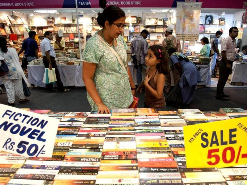 A woman looks at books accompanied by her daughter at the Delhi Book Fair in New Delhi. (AP Photo/Tsering Topgyal)