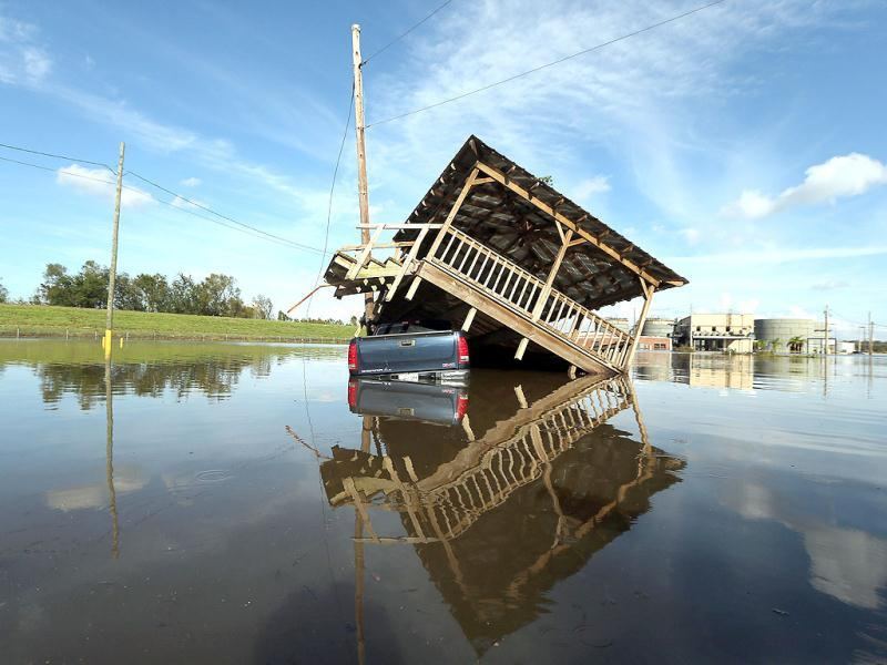 A partially submerged truck and gazebo are seen in Hurricane Isaac's flood waters with a flooded chemical plant in the background in Braithwaite, Louisiana. Mario Tama/Getty Images/AFP
