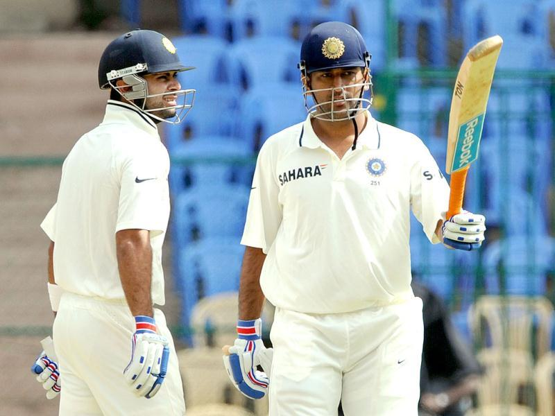 Virat Kohli (L) looks on as captain Mahendra Singh Dhoni raises his bat after scoring half a century during the third day of the second Test match in Bangalore. (AFP Photo/Manjunath Kiran)