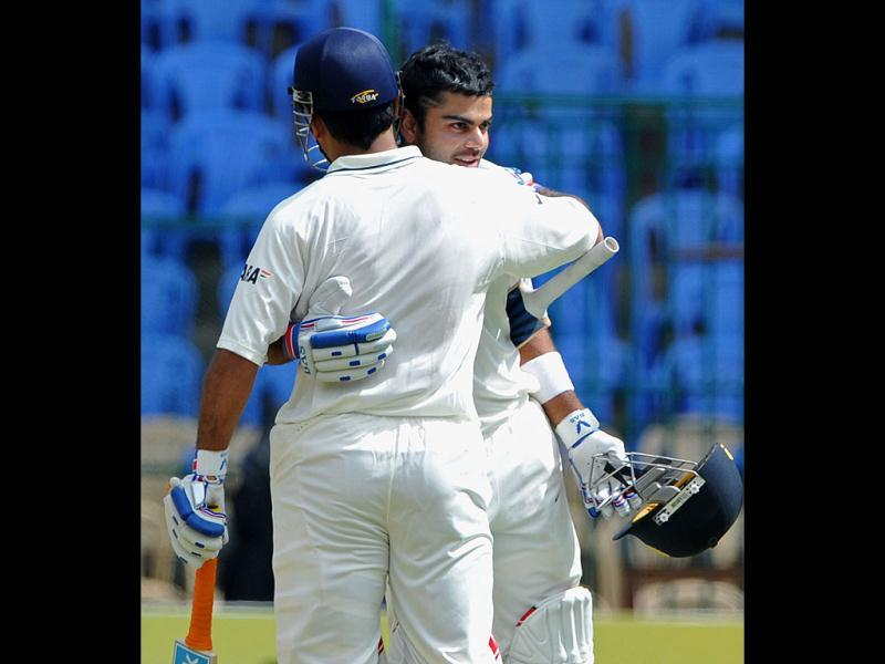 Virat Kohli (R) hugs captain Mahendra Singh Dhoni (C) after scoring a century during the third day of the second Test match between India and New Zealand in Bangalore. (AFP Photo/Manjunath Kiran)