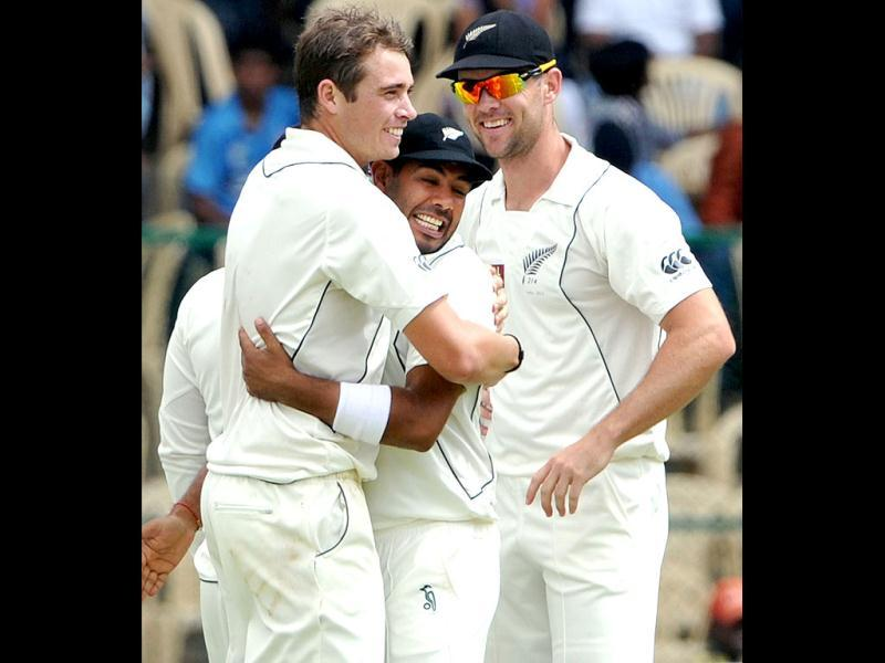 New Zealand bowler Tim Southee (L) hugs teammate Jeetan Patel after he dismissed Mahendra Singh Dhoni for 62 runs during the third day of the second Test match in Bangalore. (AFP Photo/Manjunath Kiran)