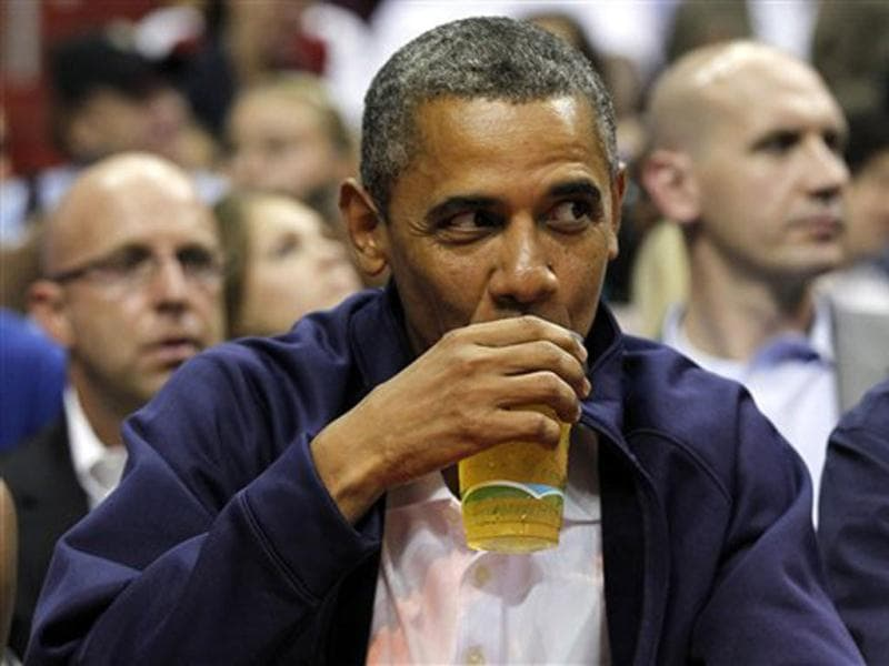 US President Barack Obama sips his beer as he watches Team USA and Brazil during the first half of an Olympic men's exhibition basketball game, in Washington. AP Photo/Alex Brandon, File