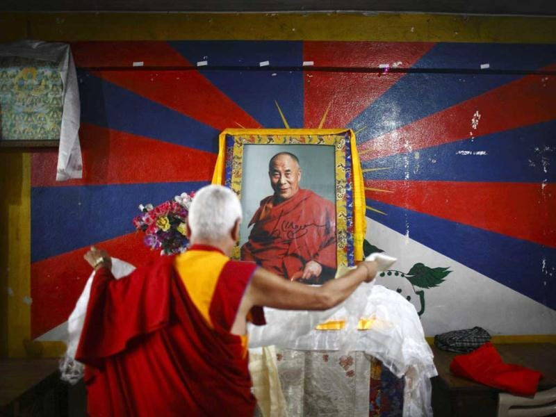 A Tibetan monk offers prayer in front of the portrait of spiritual leader Dalai Lama as he celebrates the 52nd anniversary of Tibetan Democracy Day at Tibetan Refugee Welfare Office in Kathmandhu. Reuters/UNI