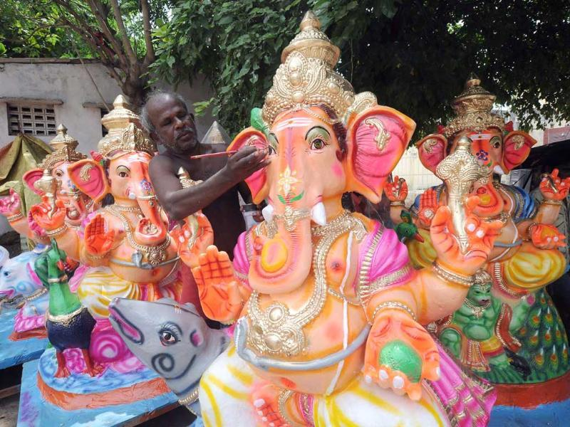 An artisan gives finishing touches to Ganesh Idols ahead of Ganesh Chaturthi in Chennai. (UNI)