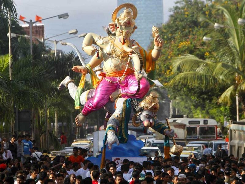 Devotees take a procession with an idol of Lord Ganesha carried by Hanuman in Mumbai. AP Photo/Rafiq Maqbool
