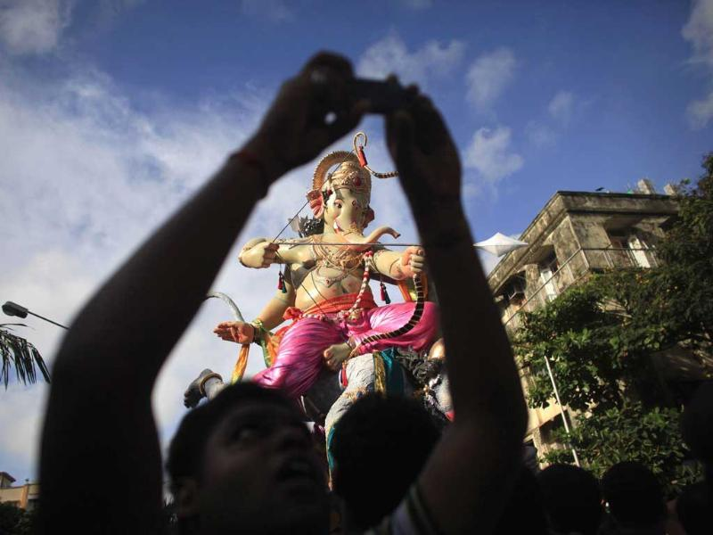 A devotee takes picture as an idol of Lord Ganesha , the deity of prosperity, is transported from a workshop to a place of worship in Mumbai. Reuters/Danish Siddiqui