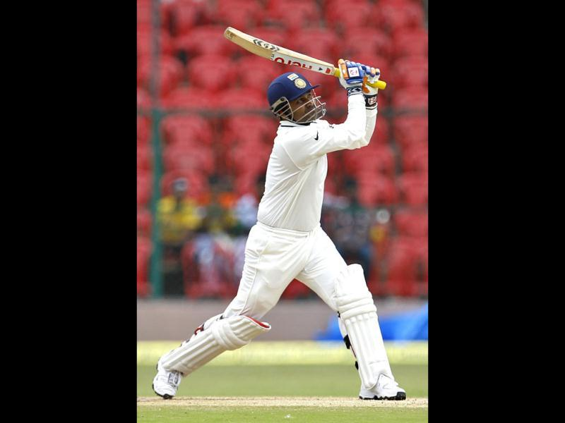 Virender Sehwag watches his shot during the fourth day of the second cricket Test match against New Zealand in Bangalore. (AP Photo/Aijaz Rahi)