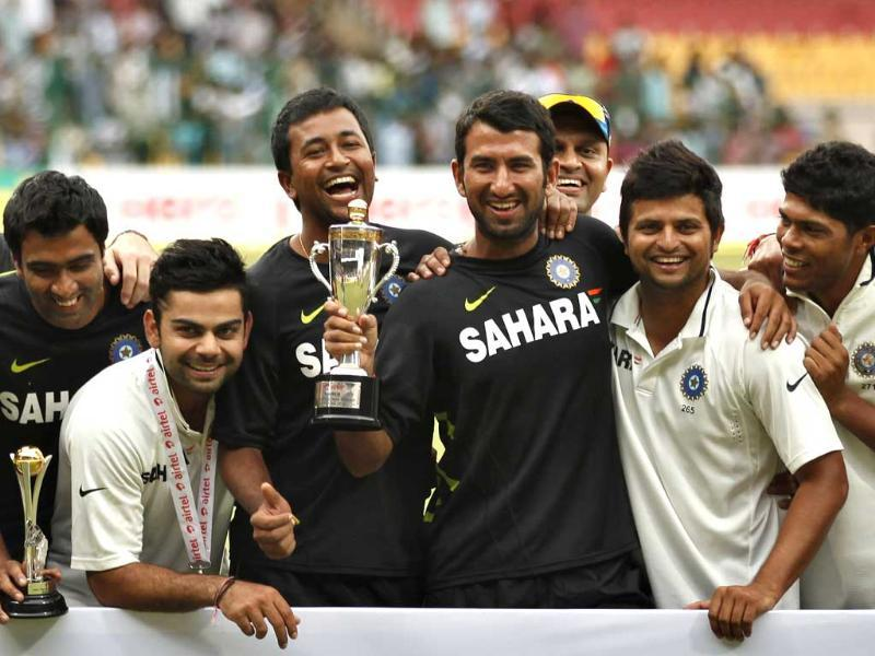 Members of Indian cricket team, from left, Ravichandran Ashwin, Virat Kohli, Pragyan Ojha, Cheteshwar Pujara, Suresh Raina and Umesh Yadav pose with the winners trophy after their win over New Zealand on the fourth day of their second cricket test match in Bangalore. (AP Photo/Aijaz Rahi)