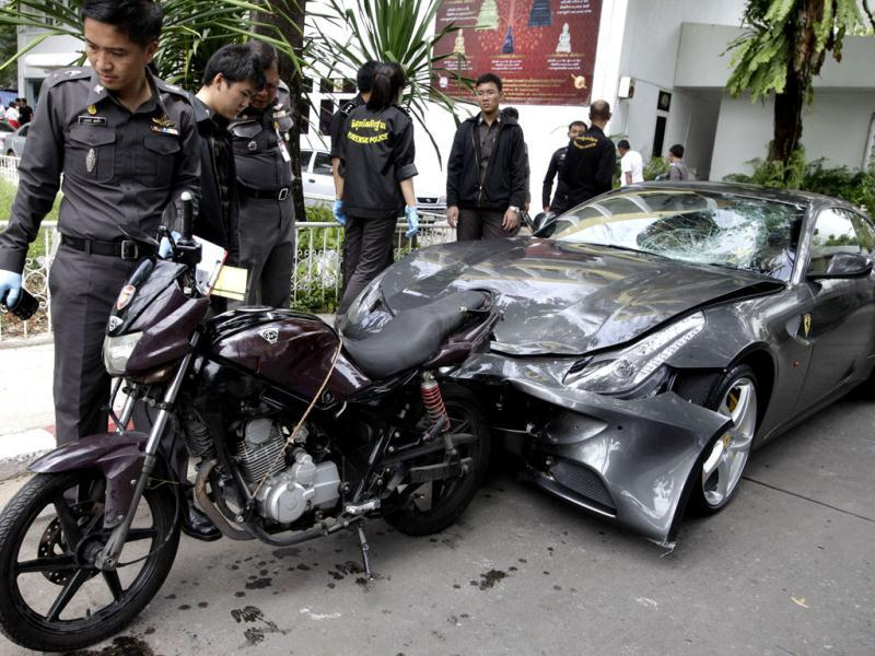 Thai police officers look at a motorcycle and a Ferrari car that involved in a hit-and-run accident during the investigation at Thong Lor police station in Bangkok, Thailand. A grandson of the creator of the Red Bull energy drink has been arrested for driving the Ferrari that struck a police officer and dragged his dead body down a Bangkok street in an early-morning hit-and-run. AP photo