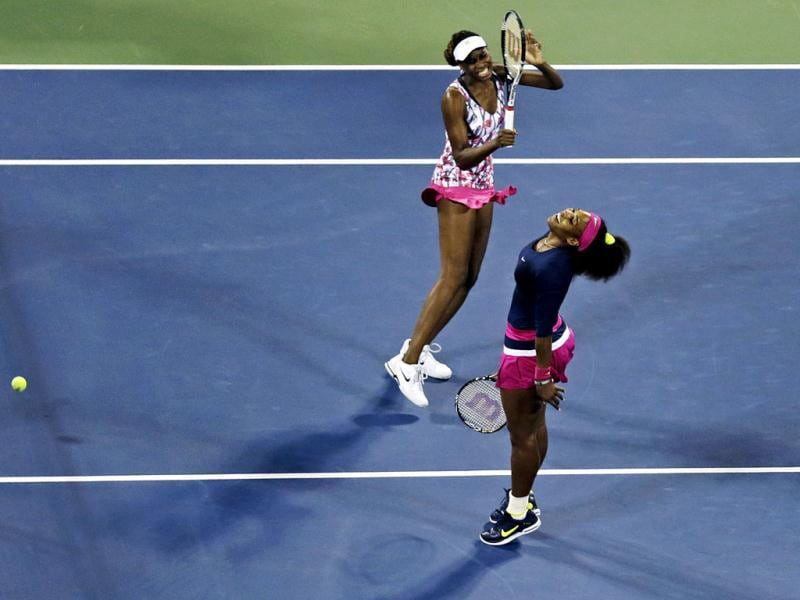 Venus Williams, left, and Serena Williams react as they miss a point during a match against Russia's Maria Kirilenko and Nadia Petrova in the third round of women's doubles play at the US Open tennis tournament in New York. Kirilenko and Petrova won 6-1, 6-4. AP photo