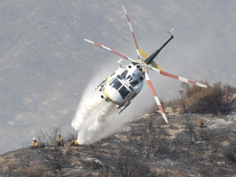 Members of a ground crew look on as a firefighting helicopter drops water on a wildfire in the Angeles National Forest north of Glendora, California. AP photo