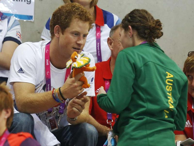 Britain's Prince Harry receives a toy of the mascot of the Australian Paralympic team from an Australian paralympian as he watches the Paralympic swimming heats during the London 2012 Paralympic Games.(Reuters/Stefan Rousseau)