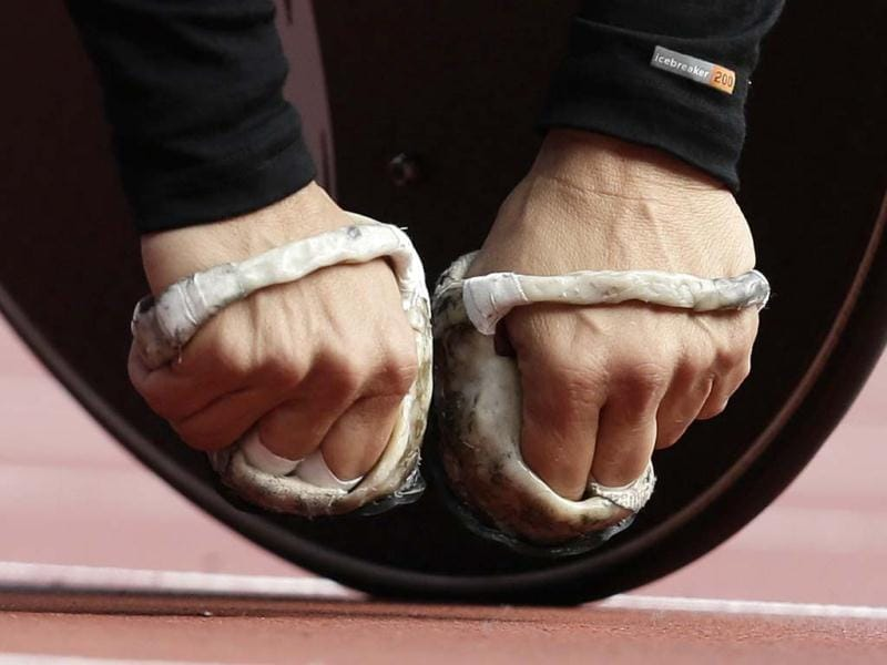 The padded hands of Diane Roy of Canada are seen as she waits to compete in the women' 800-meter T54 heat at the 2012 Paralympics games in London. The hands are padded to giver her protection as she pushes her wheelchair round the track. (AP Photo/Alastair Grant)