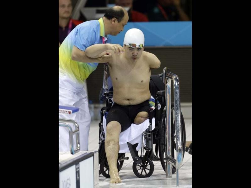 North Korea's Rim Ju Song is helped to exit the pool after competing at a men's 50m freestyle S6 heat at the 2012 Paralympics in London. (AP Photo/Lefteris Pitarakis)