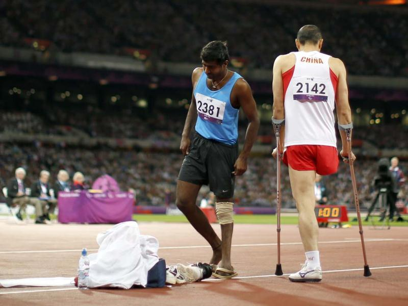 Silver medalist Girisha Hosanagara Nagarajegowda walks past China's Guo Weizhong to his belongings after jumping in the men's high jump F42 classification final during the athletics competition at the 2012 Paralympics in London. (AP Photo/Matt Dunham)