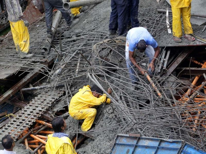 Rescuers work to remove debris after a slab of concrete from an under-construction metro bridge collapsed in Mumbai. AP Photo