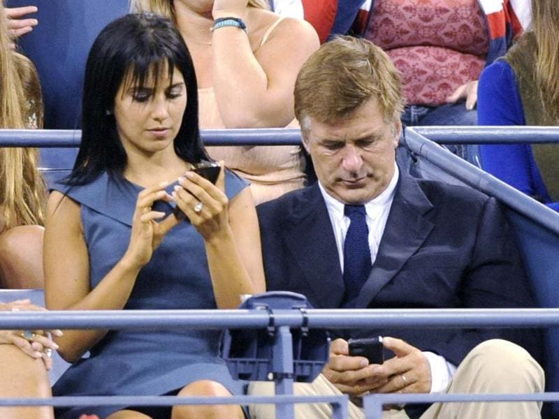 Actor Alex Baldwin (R) and wife Hilaria Thomas work on their phones as they attend the opening night matches at the US Open tennis tournament in New York. (Reuters/Bill Kostroun)