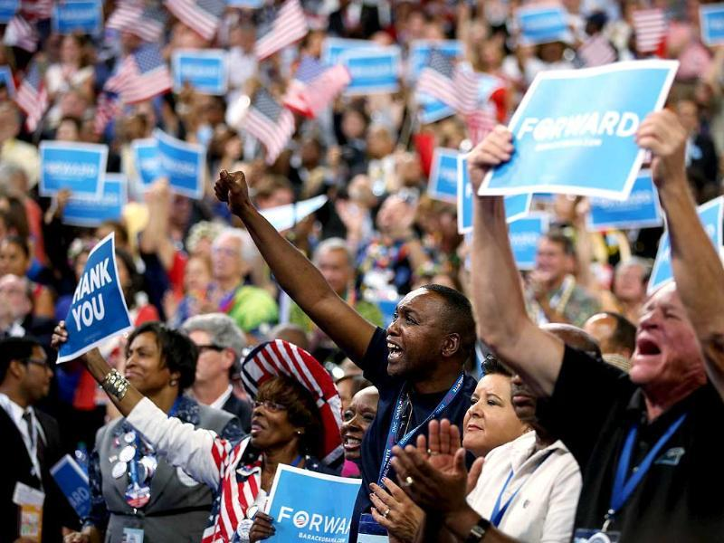 People cheer as Democratic presidential candidate, US President Barack Obama speaks on stage as he accepts the nomination for president during the final day of the Democratic National Convention at Time Warner Cable Arena in Charlotte, North Carolina. Chip Somodevilla/AFP