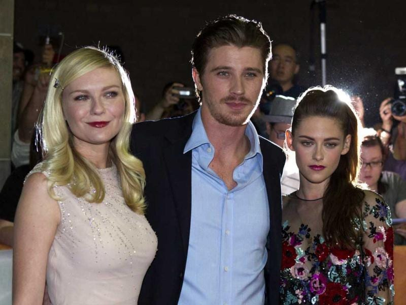 While co-stars Kirsten Dunst (L) and Garrett Hedlund pose for the cameras, Kristen looks lost and pensive.