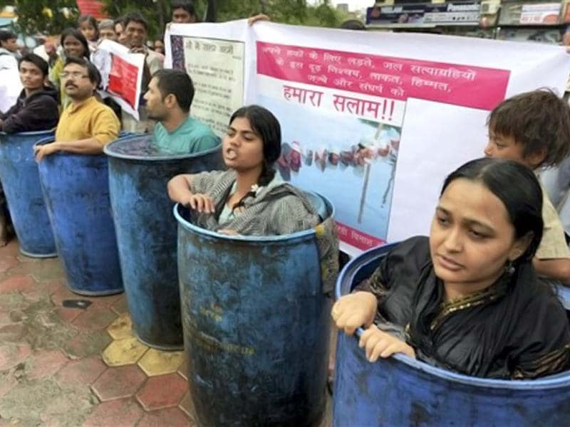 Social activists standing in water drums in Bhopal during their protest to support the indefinite 'Jal Satyagrah' agitation of the oustees of Omkareshwar Dam at Narmada river . PTI Photo