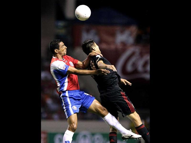 Mexico's Oribe Peralta jumps for the ball against Costa Rica's Michael Umana during their 2014 World Cup qualifying soccer match at the National Stadium in San Jose. (Reuters)