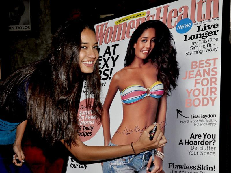 Lisa Haydon signs across her image on the cover.