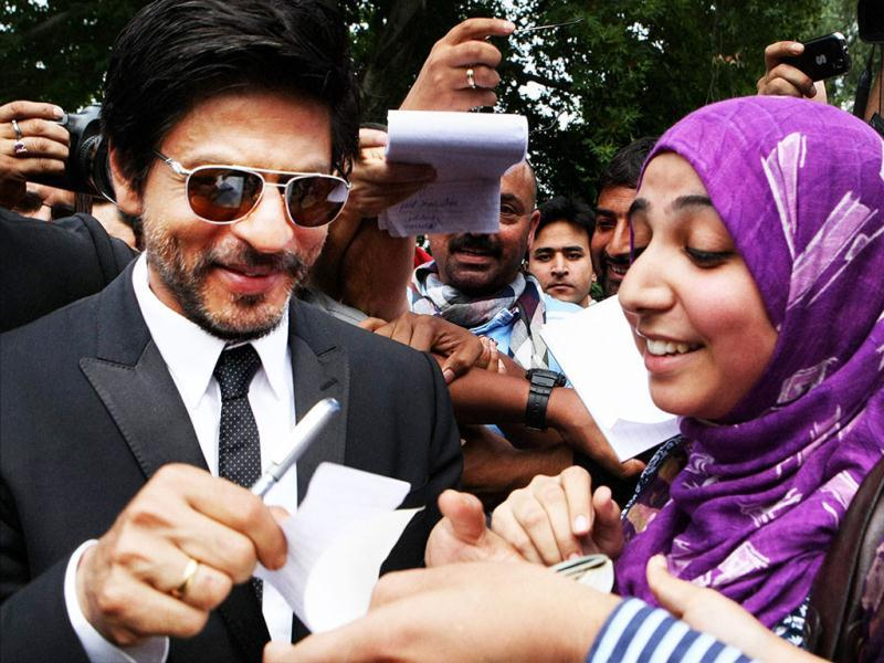 Bollywood actor SRK is all smiles while signing an autograph.