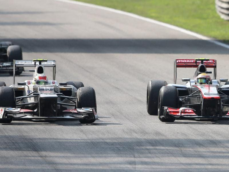 McLaren Mercedes driver Lewis Hamilton of Britain, right, steers his car alongside Sauber driver Sergio Perez of Mexico, on his way to win the Italian Formula One GP, at the Monza racetrack, Italy. AP Photo/Alessandro Trovati