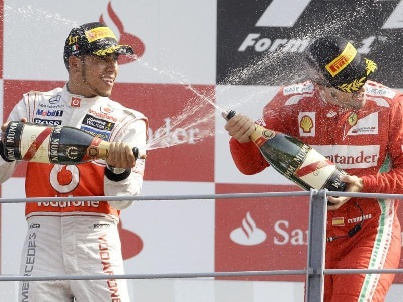 McLaren Mercedes driver Lewis Hamilton, left, of Britain, celebrates with third placed Ferrari driver Fernando Alonso, of Spain, after winning the Italian Formula One GP, at the Monza racetrack, in Monza, Italy. AP Photo/Antonio Calanni