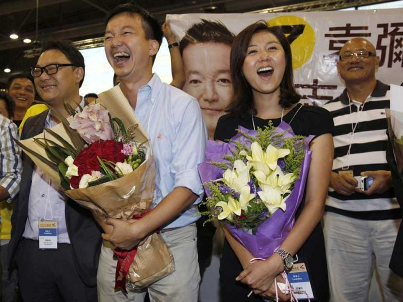 Former Miss Hong Kong contestant and Legislative Council election candidate Erica Yuen (2nd R) and her election partner, former radio disc jockey Ray Chan (2nd L) from the pro-democracy People Power react at the central ballot counting centre in Hong Kong. Chan won in the election and Yuen lost. Political allies of Hong Kong's new Beijing-backed leader performed solidly in city-wide legislative council elections despite recent controversies over contentious China-linked policies, potentially easing pressure on his administration.  REUTERS/Bobby Yip