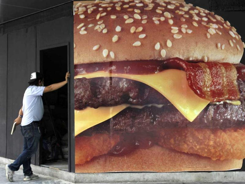 A Thai worker stands outside a new hamburger shop during its renovation in Bangkok. (AP Photo/Sakchai Lalit)