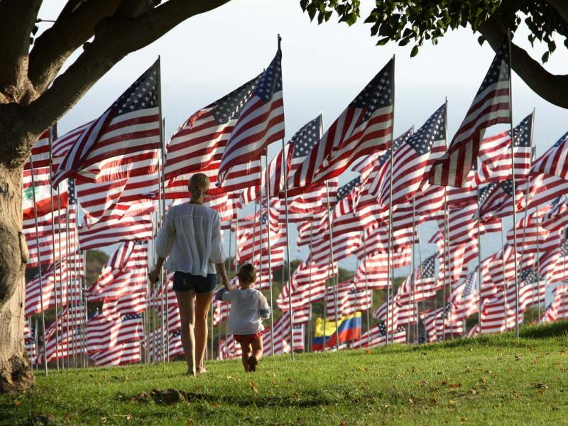 Dominique Sanders walks with her two-and-a-half year old daughter Roux among flags flying at Pepperdine University in honor of the victims of the September 11, 2001 attacks in Malibu, Calif. (AP Photo/David McNew)