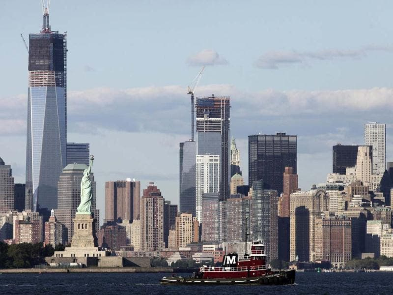 A tugboat passes the World Trade Center in New York and the Statue of Liberty marking the 11th anniversary of the terrorist attacks. The tallest tower is 1 World Trade Center, now up to 105 floors. and to the right is 4 World Trade Center, also under construction. (AP Photo/Mark Lennihan)
