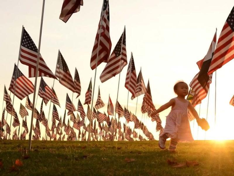 A child walks amongst US national flags erected by students and staff from Pepperdine University to honour victims of the 9/11 attacks, in Malibu. (AFP/ Joe Klam