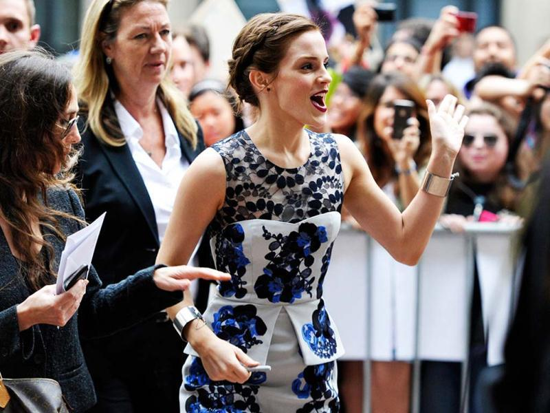 Emma Watson signs autographs and poses for fans.