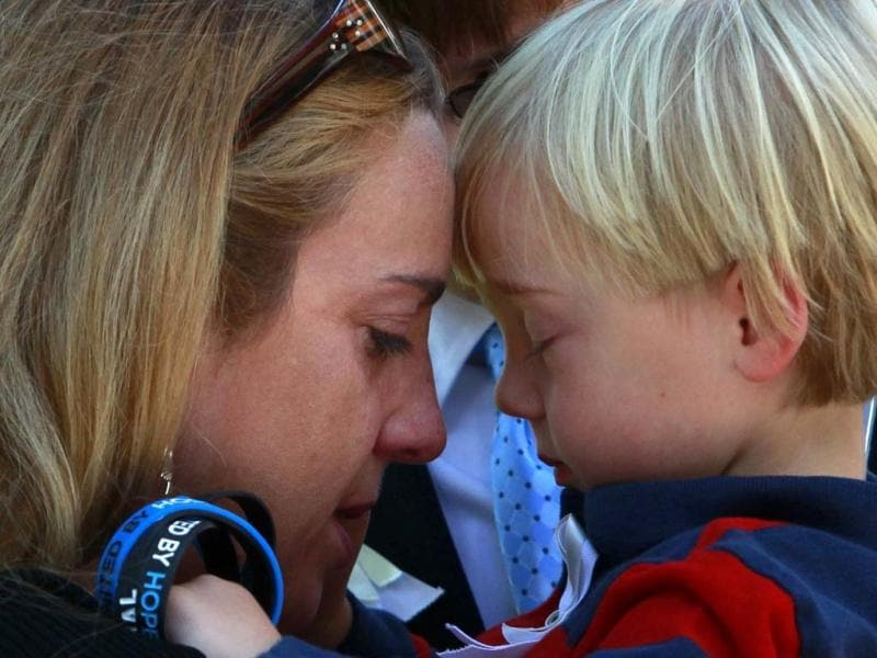 A woman embraces a child at the site of the 9/11 memorial during ceremonies marking the 11th anniversary of the 9/11 attacks on the World Trade Center in New York. (Reuters/Eric Thayer)