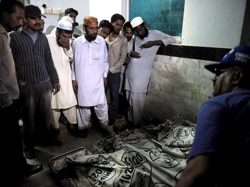 Pakistani people identify the dead bodies of workers after a garment factory was engulfed in a fire in Karachi. At least 63 people were killed when a blaze engulfed a garment factory in Pakistan's largest city Karachi, an official said. (AFP/Asif Hassan)