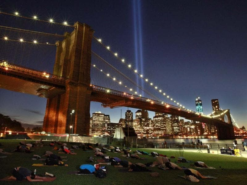 People take part in a sunset yoga session as the Tribute in Light shines over the Brooklyn Bridge over the East River on the 11-year anniversary of the 9/11 attacks in New York. (Reuters/Brendan McDermid)