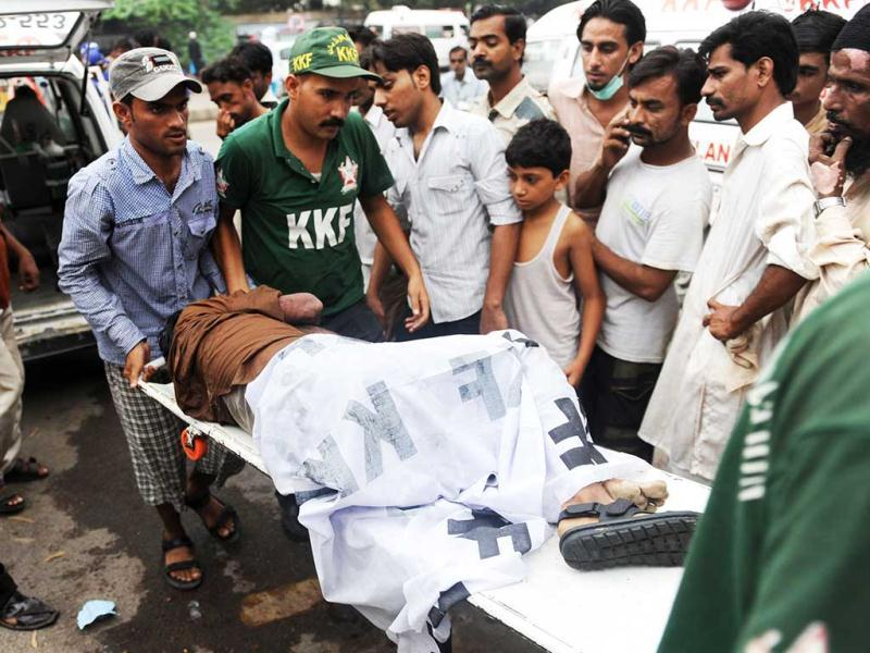 Pakistani rescuers move the dead body of a garment labourer who was killed after fire erupted at a factory in Karachi. (AFP/Rizwan Tabassum)