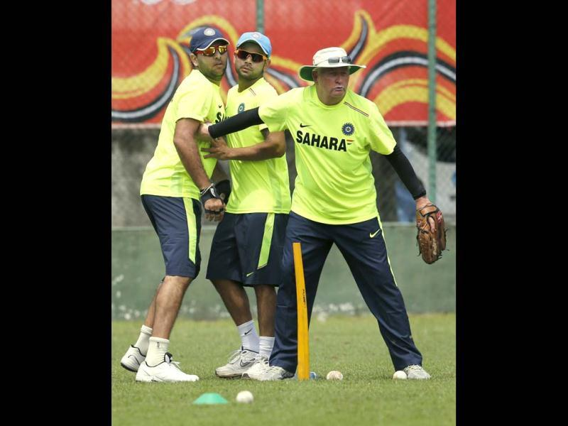 Team India coach Duncan Fletcher pushes backYuvraj Singh and Suresh Raina during a practice session ahead of the Twenty20 World Cup cricket tournament in Colombo, Sri Lanka. AP Photo/Eranga Jayawardena