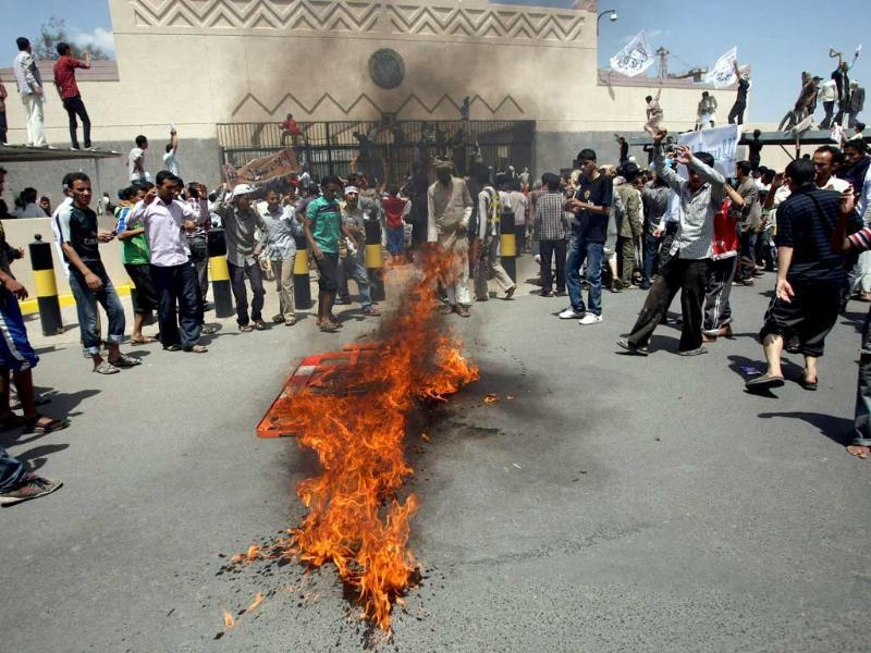 Yemeni protesters gather around fire during a demonstration outside the US embassy in Sanaa over a film mocking Islam. Yemeni forces managed to drive out angry protesters who stormed the embassy in the Yemeni capital with police firing warning shots to disperse thousands of people as they approached the main gate of the mission.  AFP PHOTO/MOHAMMED HUWA