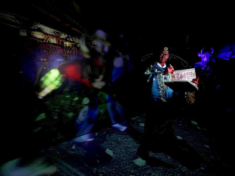 An actor dressed as a Chinese hell judge stands in front of a screen inside a 5D haunted house at the Hong Kong Ocean Park. Reuters Photo