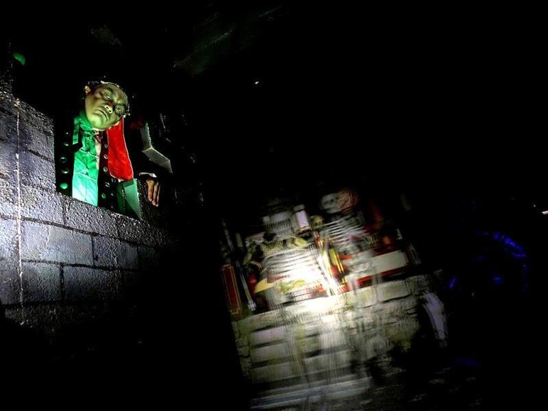 An actor dressed as a ghost emerges in front of a screen inside a 5D haunted house at the Hong Kong Ocean Park. Reuters Photo