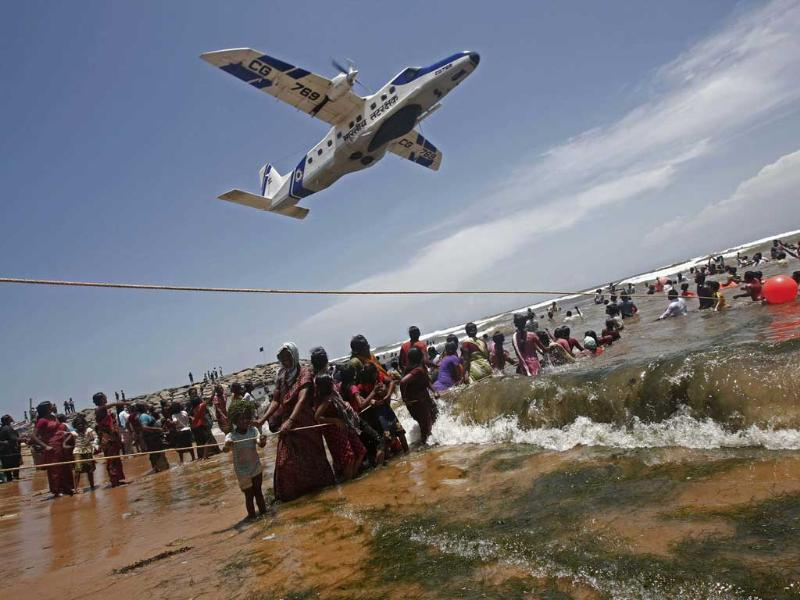 A plane flies over the demonstrators as they hold on to ropes while standing in waters of the Bay of Bengal during a protest near Kudankulam nuclear power project in Tamil Nadu. Reuters/Adnan Abidi