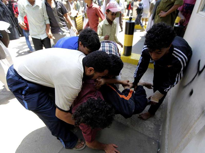 Medics carrying a protester injured during a demonstration at the US embassy in Sanaa. Reuters/Mohamed al-Sayaghi