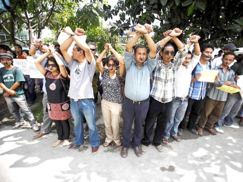 Artists, with their lips sealed with tape, raise their hands which are handcuffed using tape in a protest demanding the safety of artist Manish Harijan and his freedom of expression, near the Kathmandu District Administration Office (DAO) in Kathmandu. (Reuters)